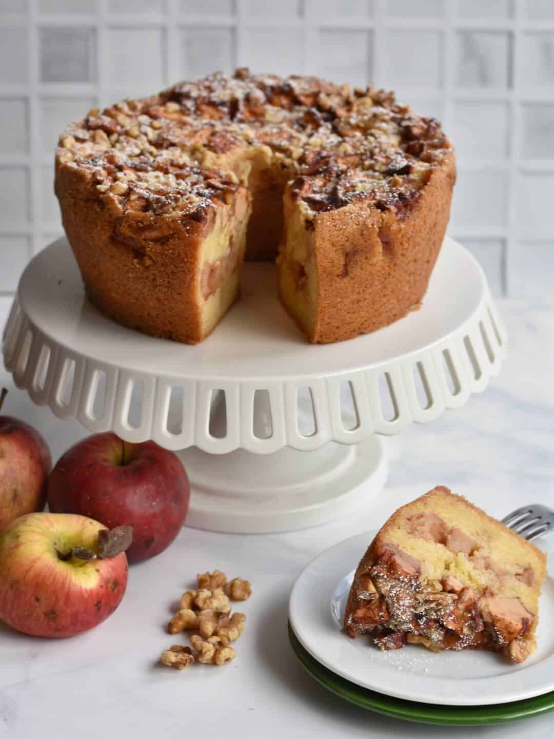 apple cake on a cake stand with slice on a plate