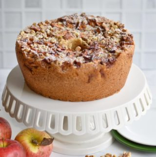 apple cake on cake stand with apples in foreground
