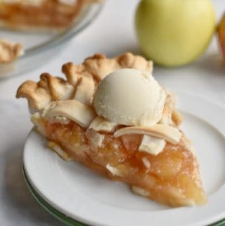 Homemade apple pie on a plate with ice cream.