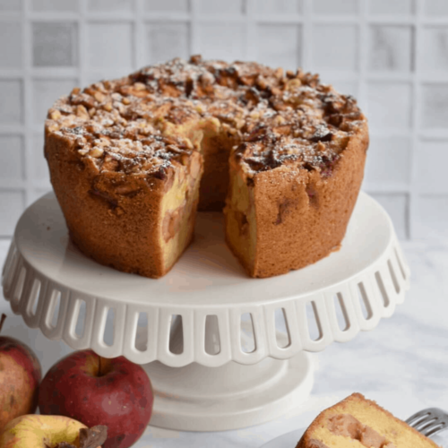apple cake on a cake stand with a slice cut out