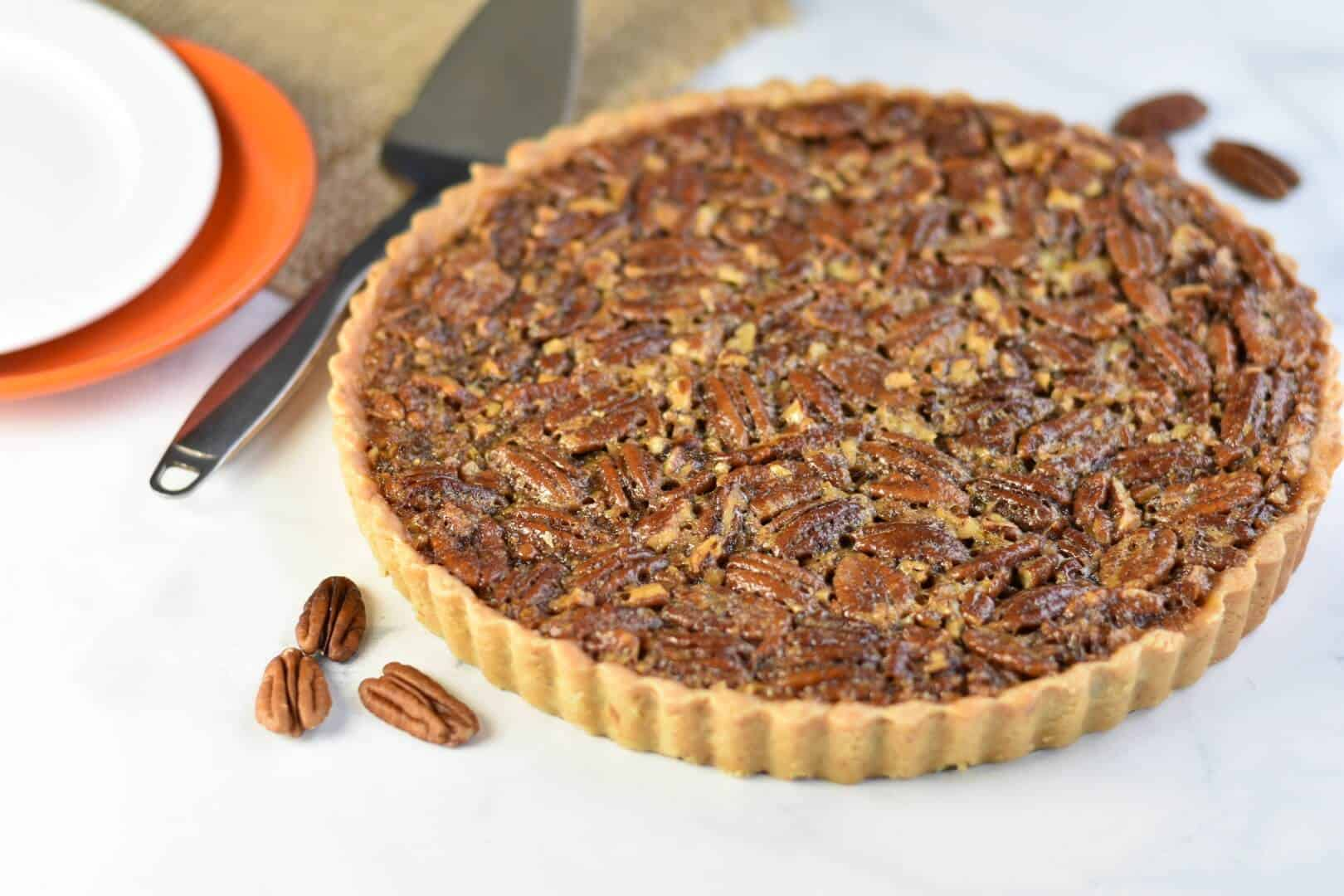 entire pecan tart shot from above with serving spoon