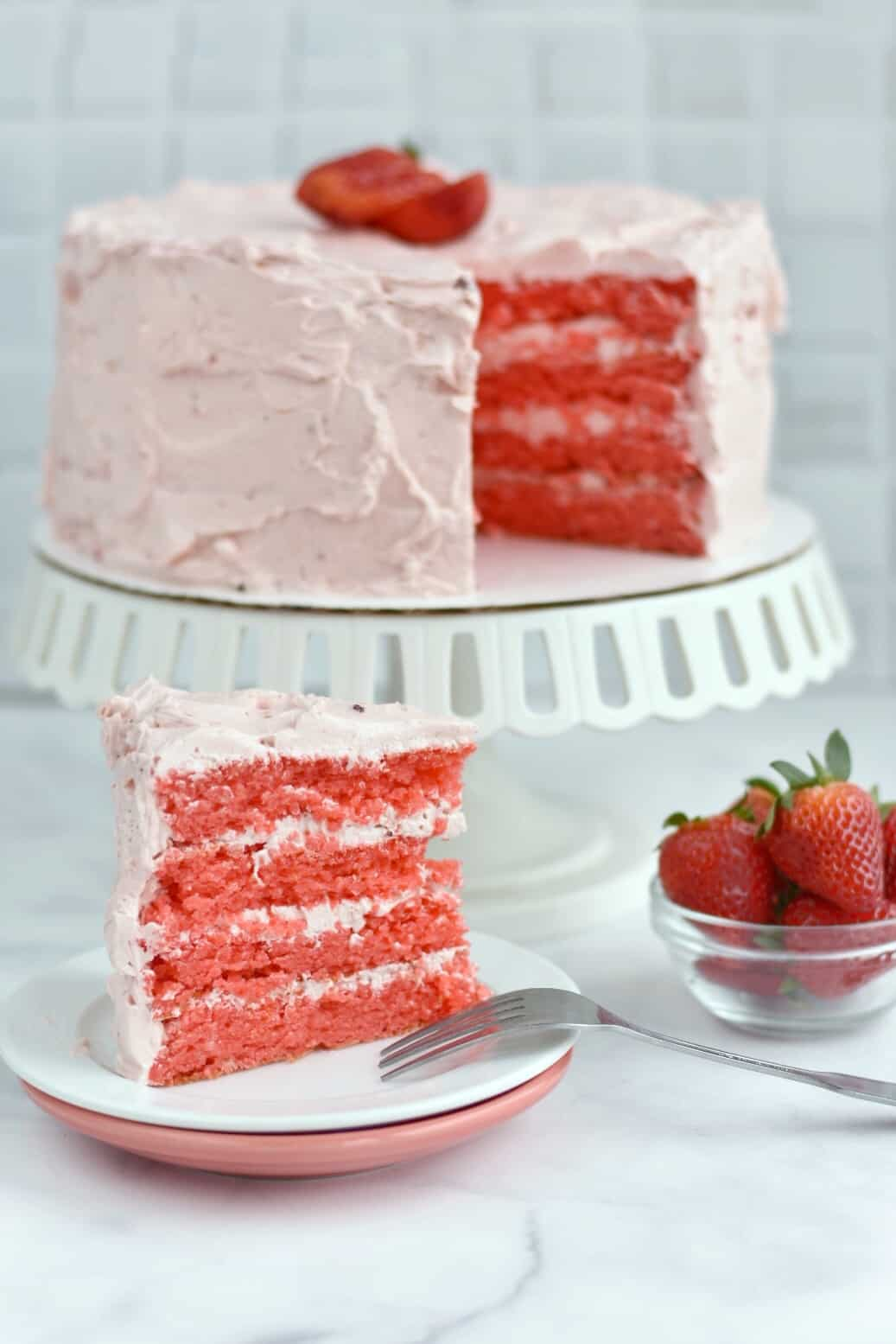 slice of strawberry cake with entire cake in background