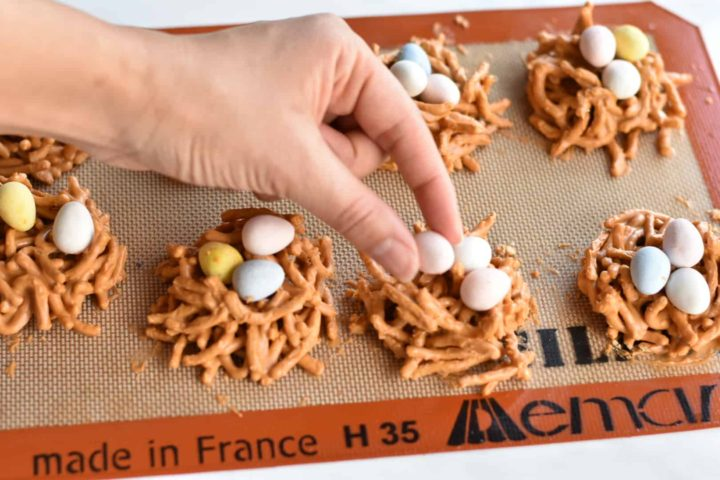hand placing an egg on birds nest cookies