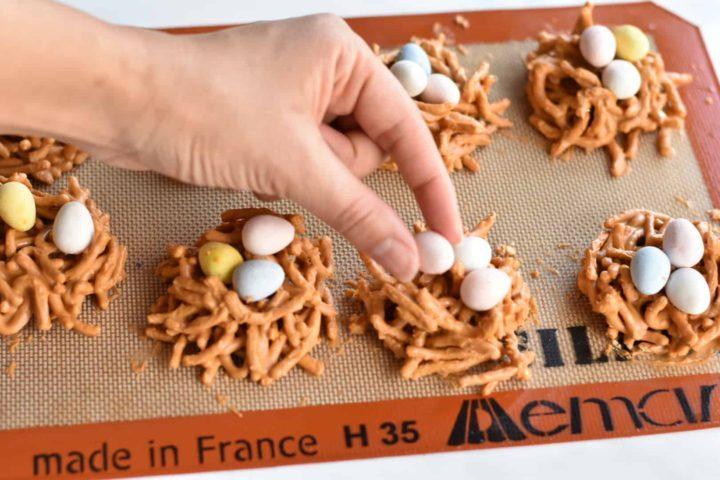 hand placing an egg on birds nest cookies