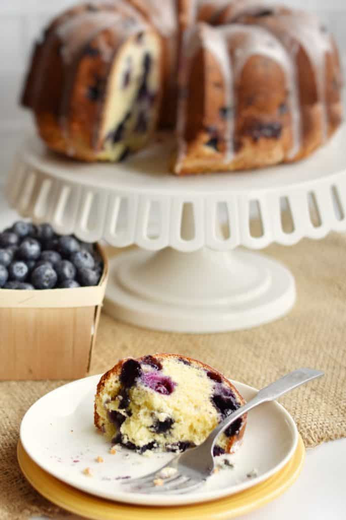 closeup of lemon blueberry cake slice with blueberries in background