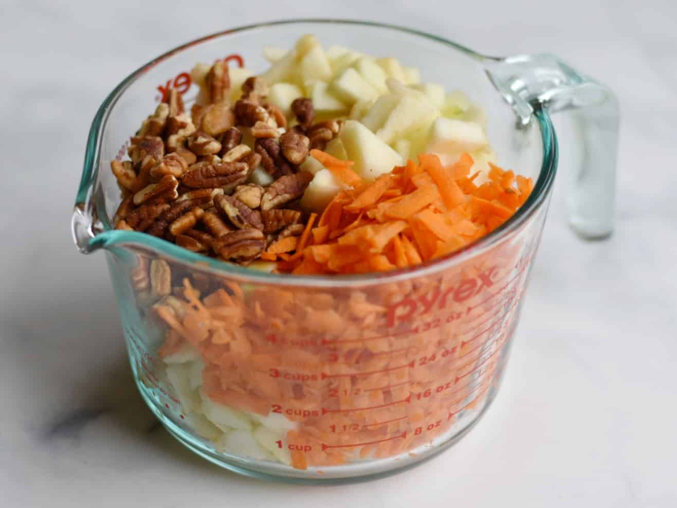 apples, pecans, and carrots in measuring cup