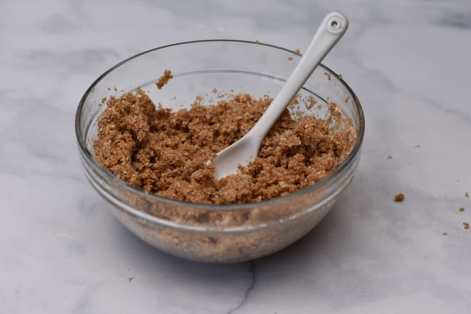 skim milk and oat bran mixed together in bowl with white spoon