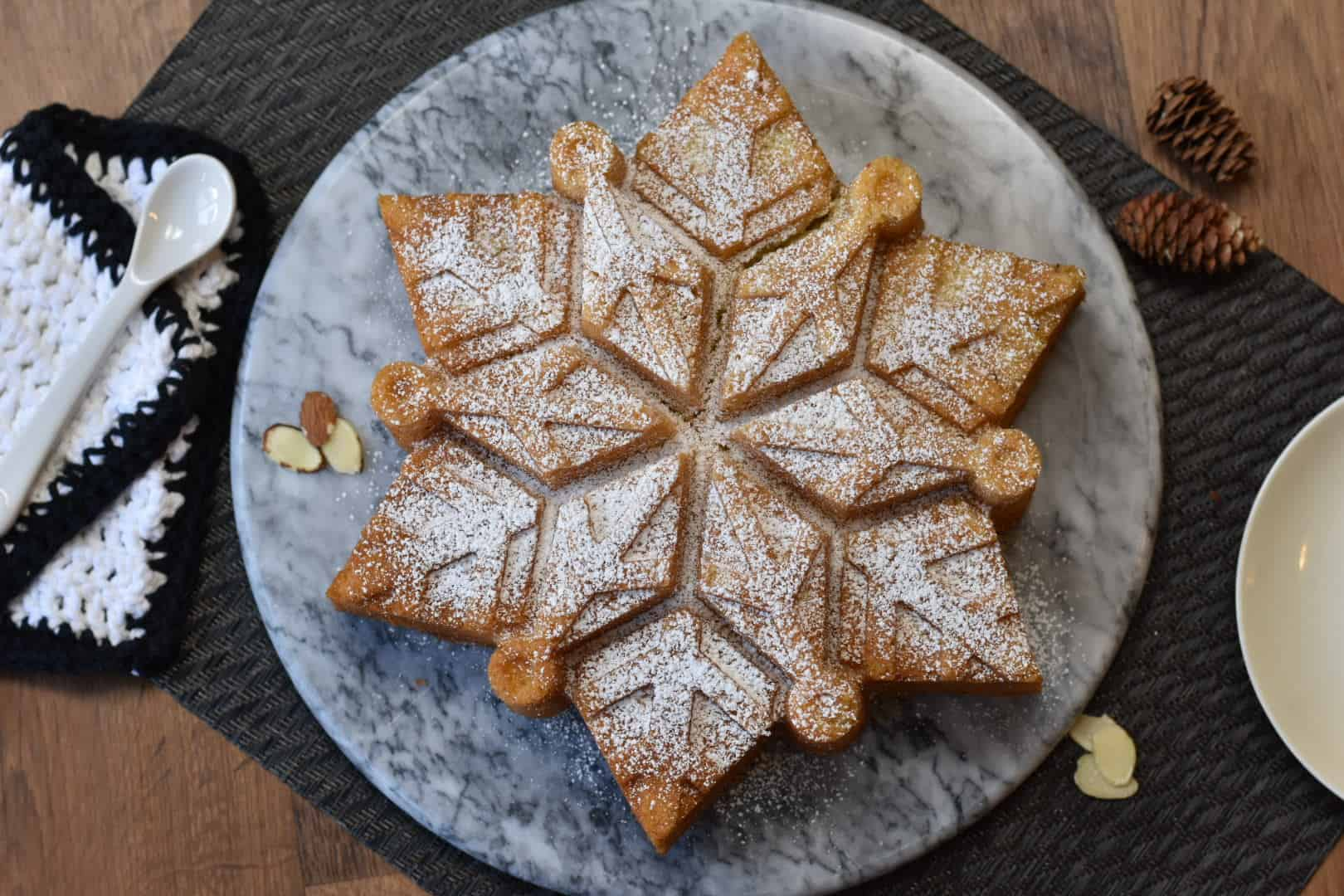 almond snowflake cake sitting on platter viewed from above