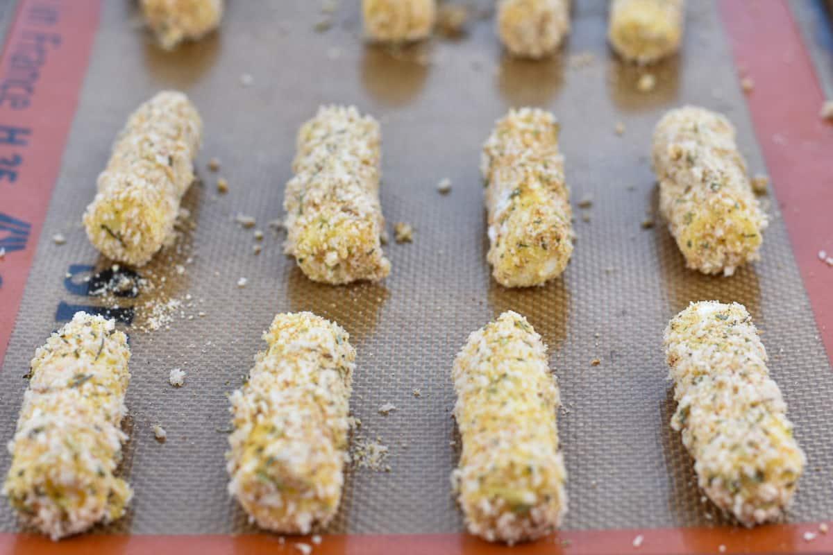 baked mozzarella sticks on baking sheet