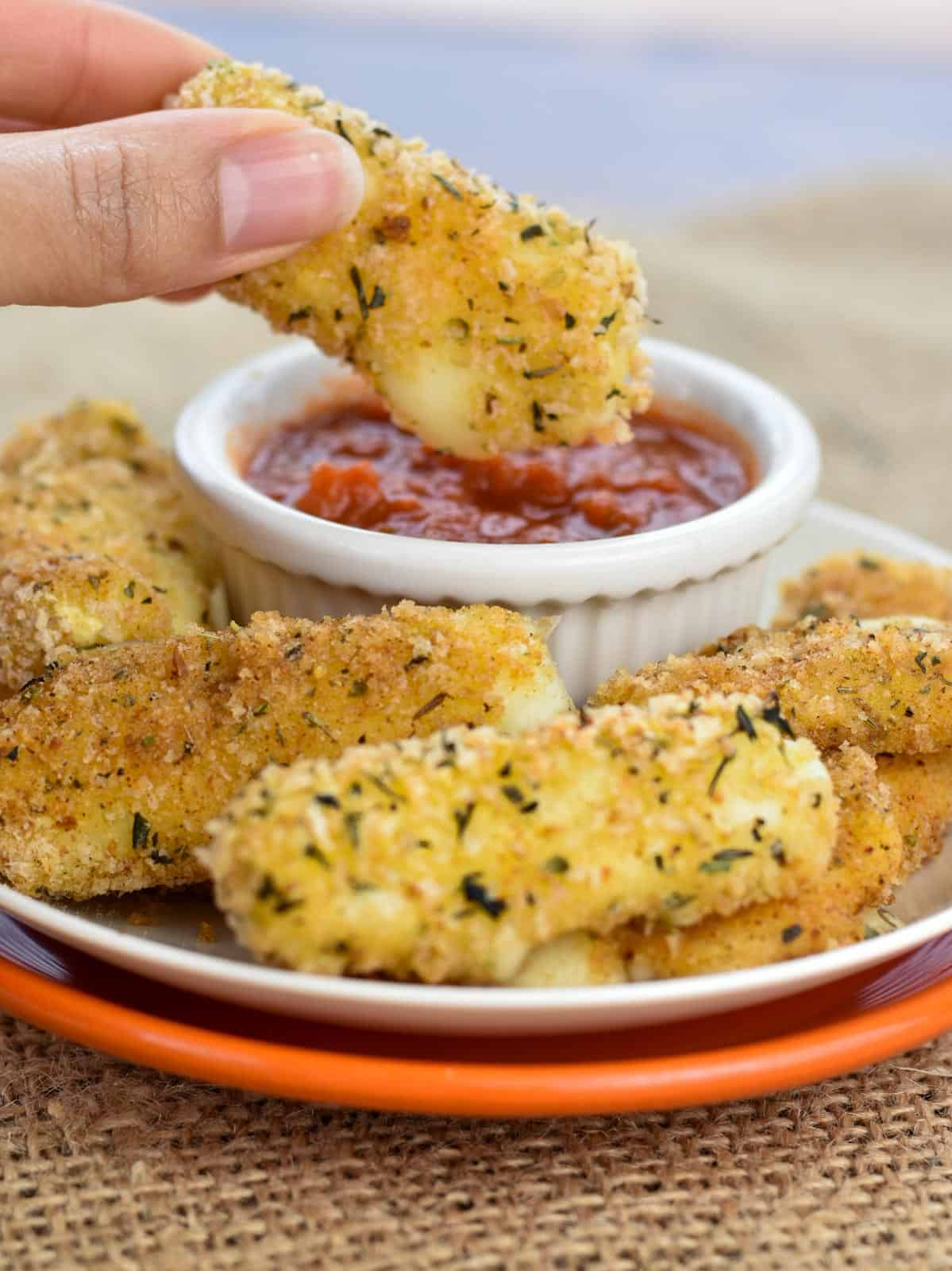 hand dipping a baked mozzarella stick in marinara sauce