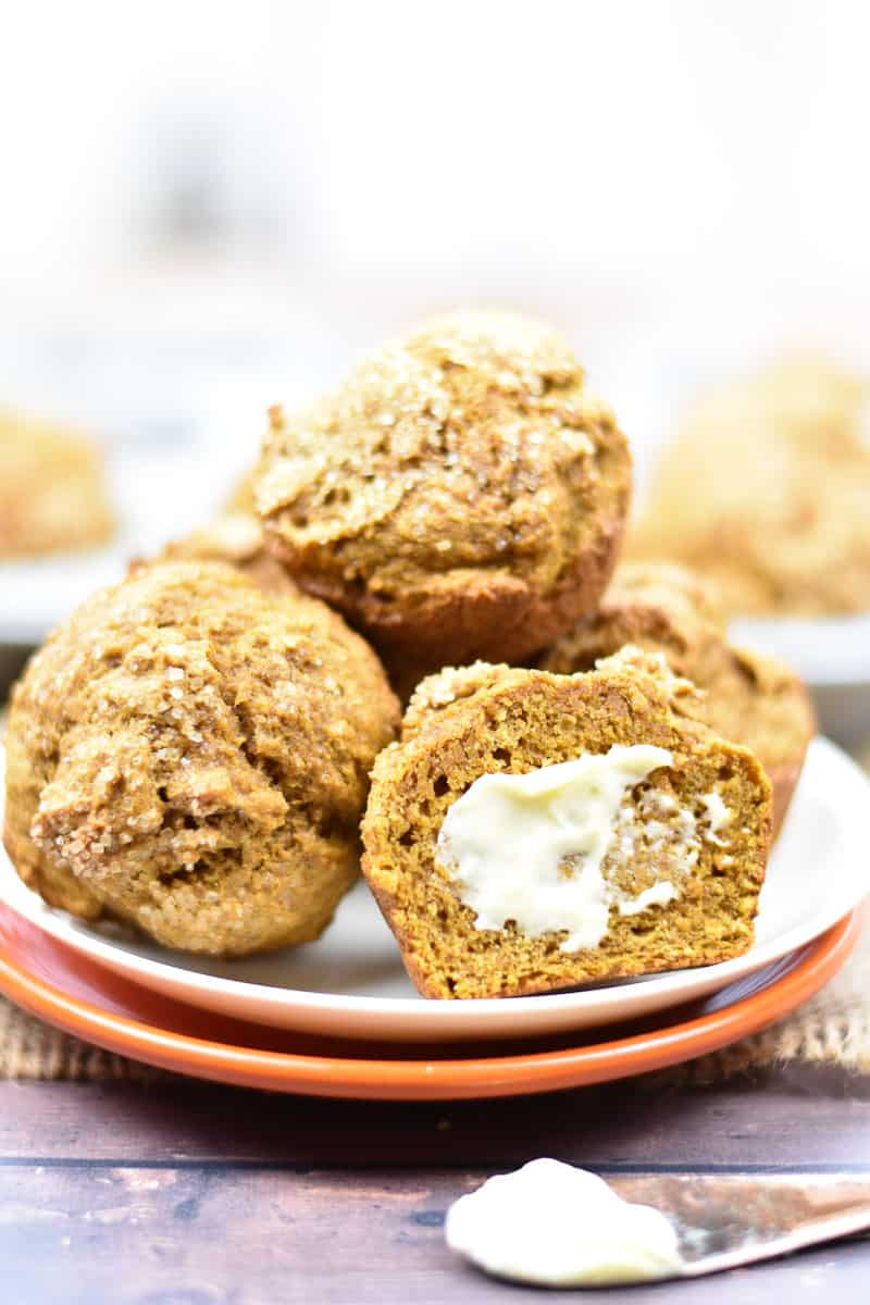pumpkin muffins stacked on a plate with butter spread on top