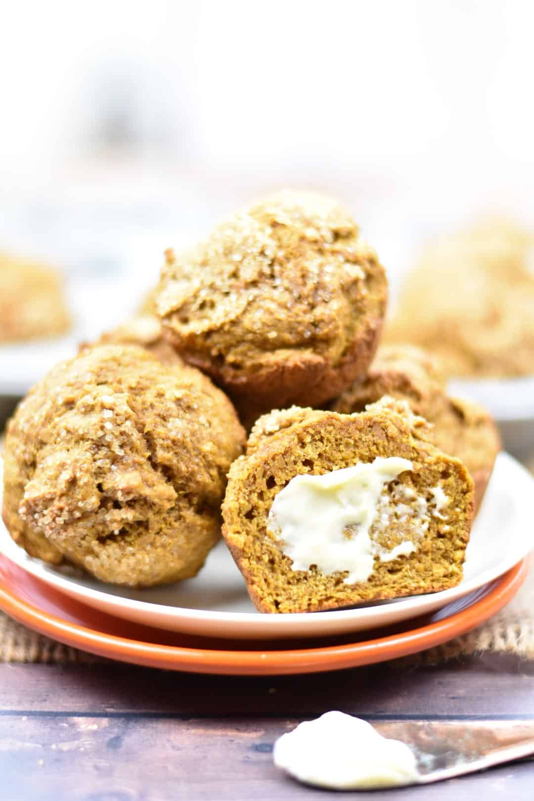closeup of whole wheat pumpkin muffins on a plate with butter