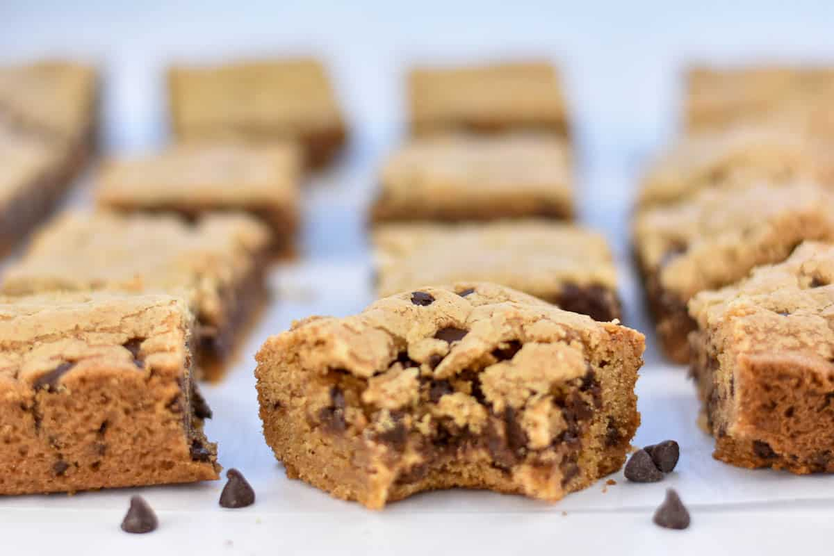 chocolate chip cookie butter blondies on table with a bite out of one