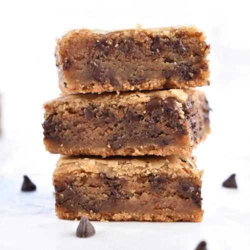 closeup image of three stacked chocolate chip cookie butter blondies