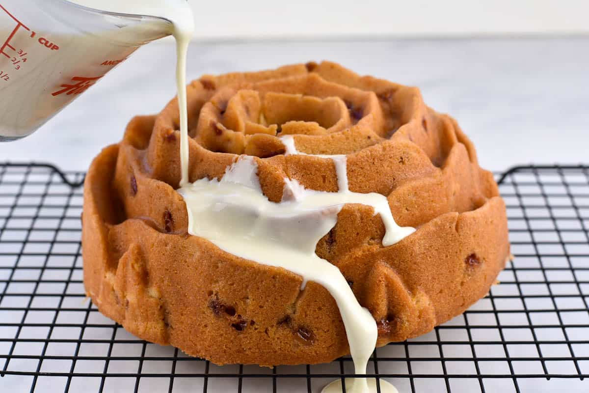 pouring cream cheese frosting over cake for glaze