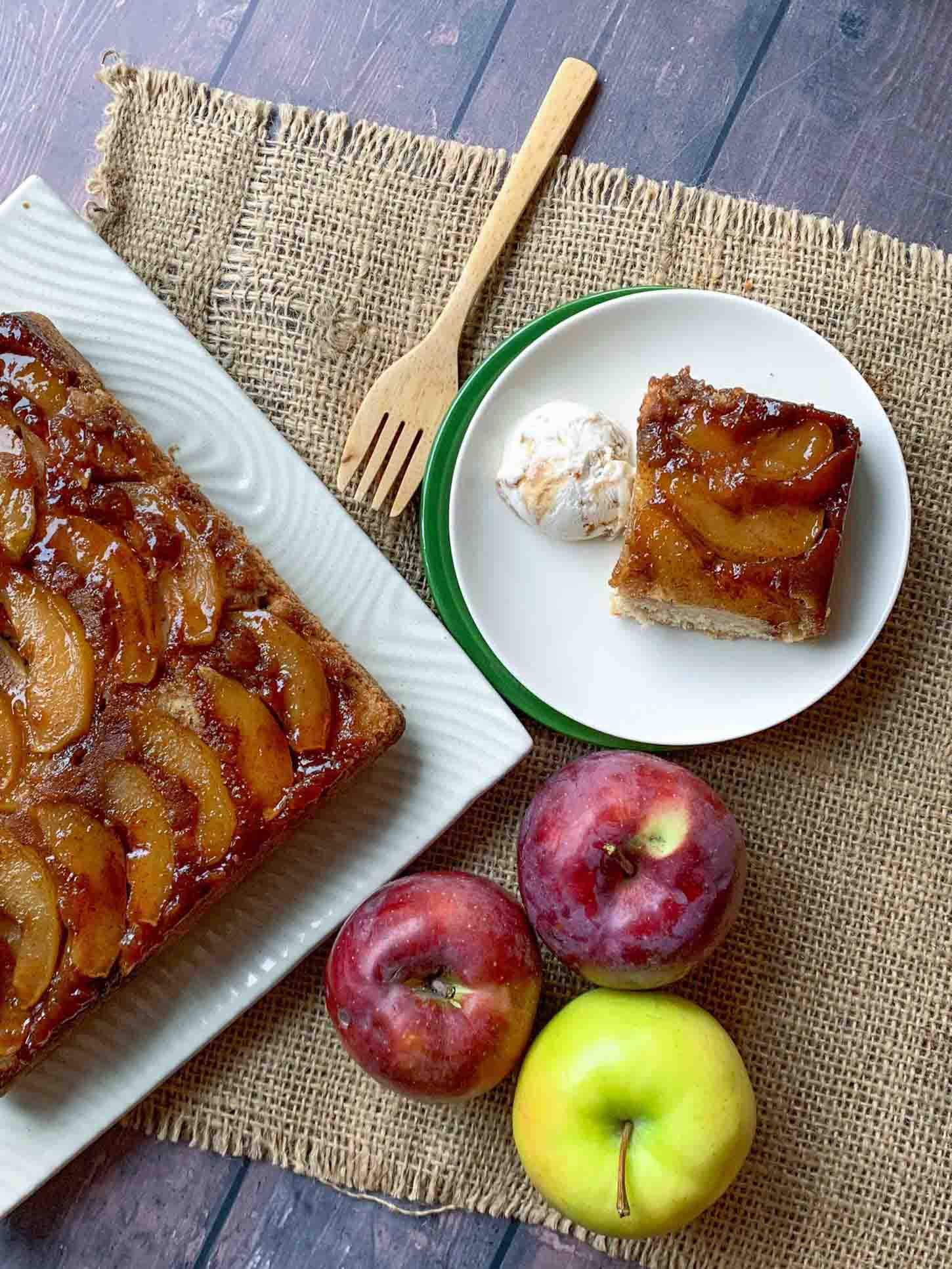 overhead picture of apple cinnamon upside-down cake on a platter with a cake slice on a plate