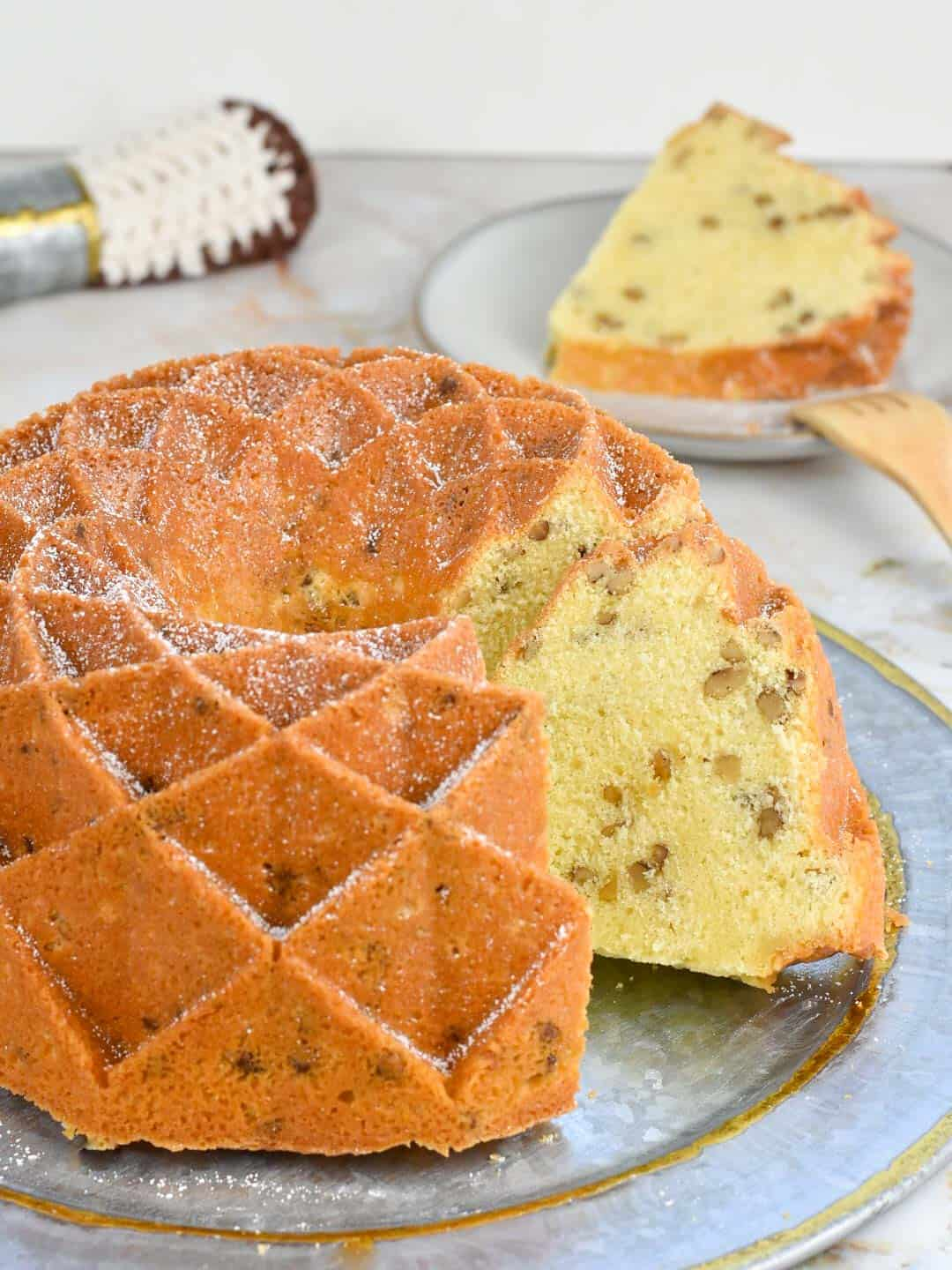 image of black walnut pound cake on a platter with a slice in the background