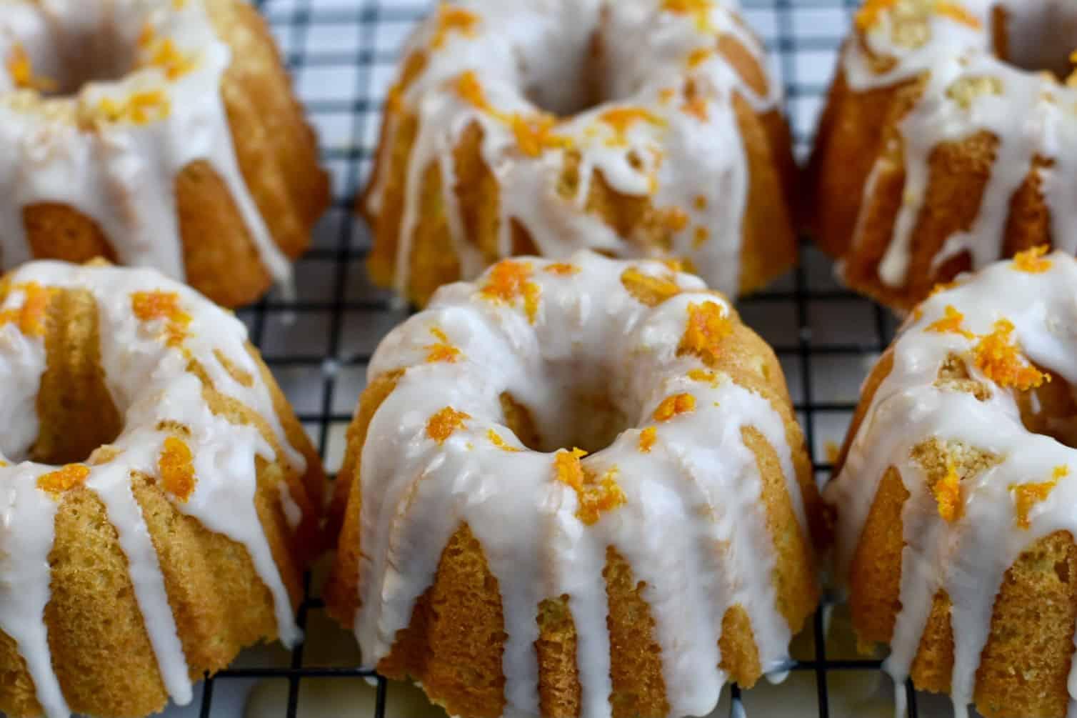 mini bundt cakes on cooling rack with glaze and orange zest