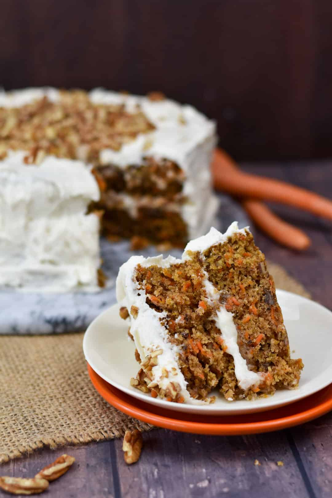 closeup shot of pecan carrot cake slice on a plate