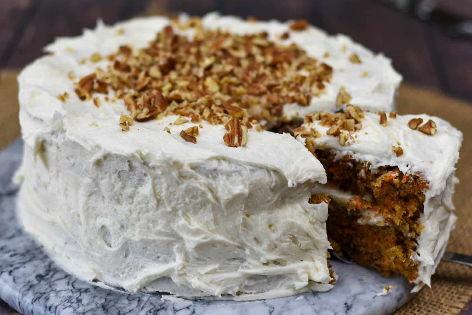 slice of carrot cake being removed from cake