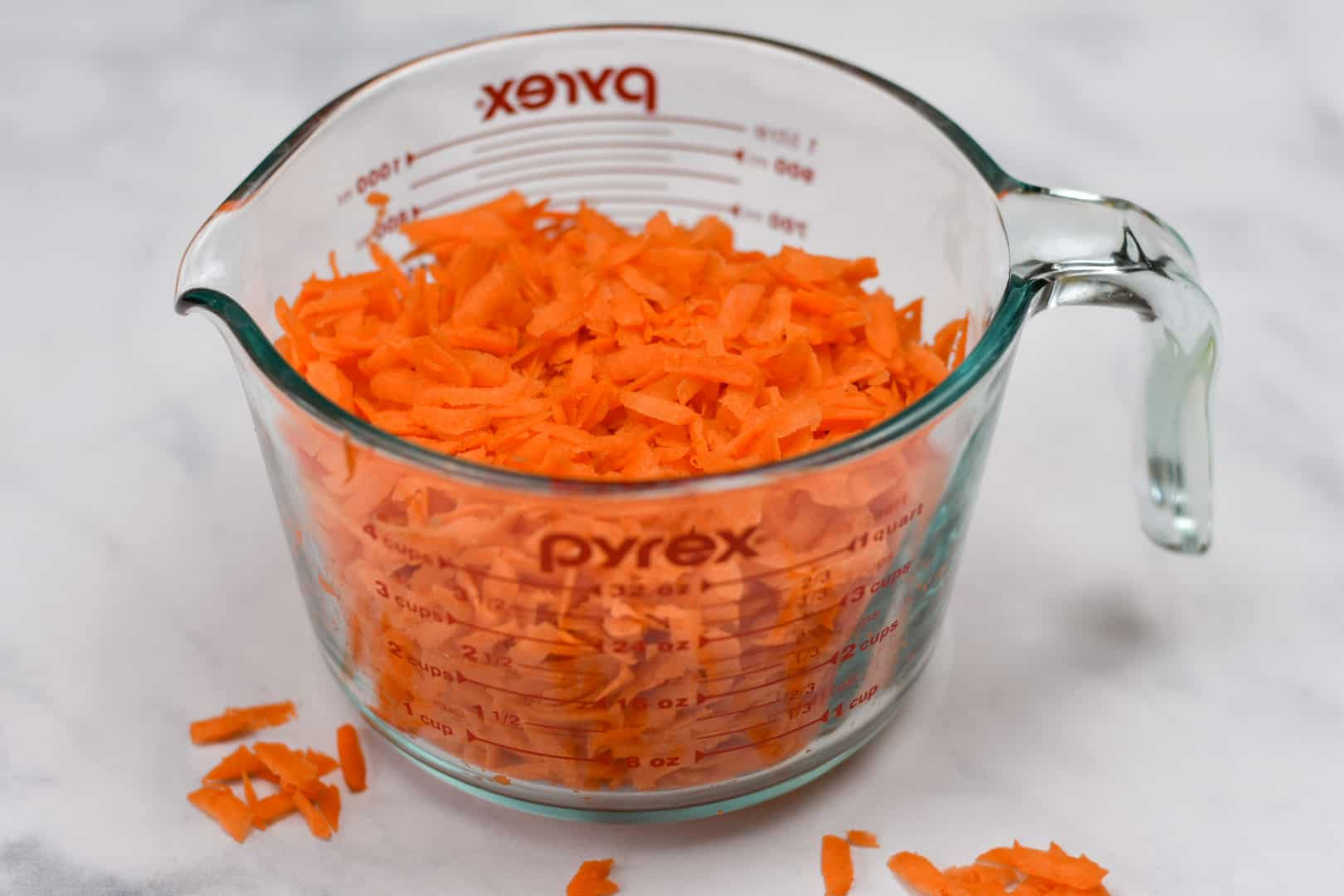 shredded carrots in a measuring cup