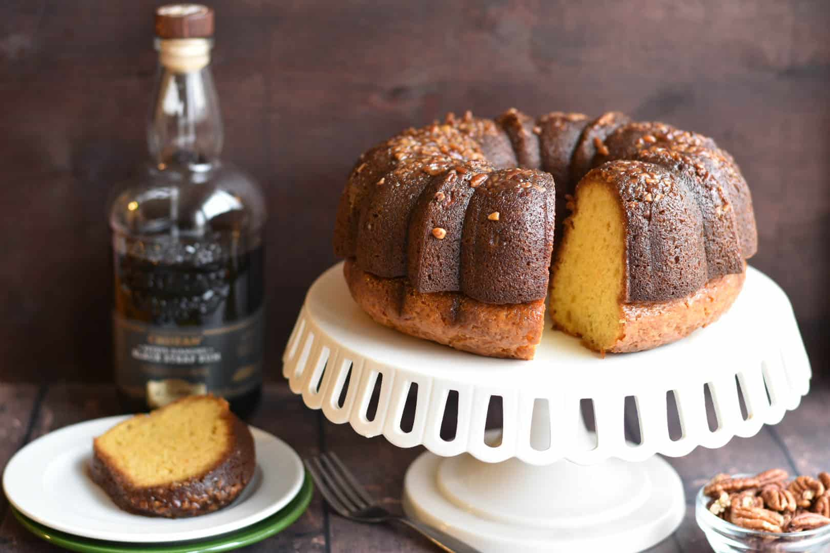 pecan rum cake on a platter with slice on plate