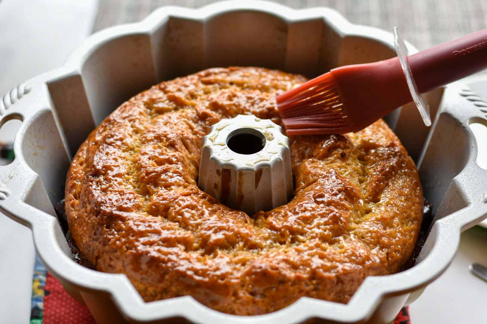 cake in bundt pan with glaze being applied