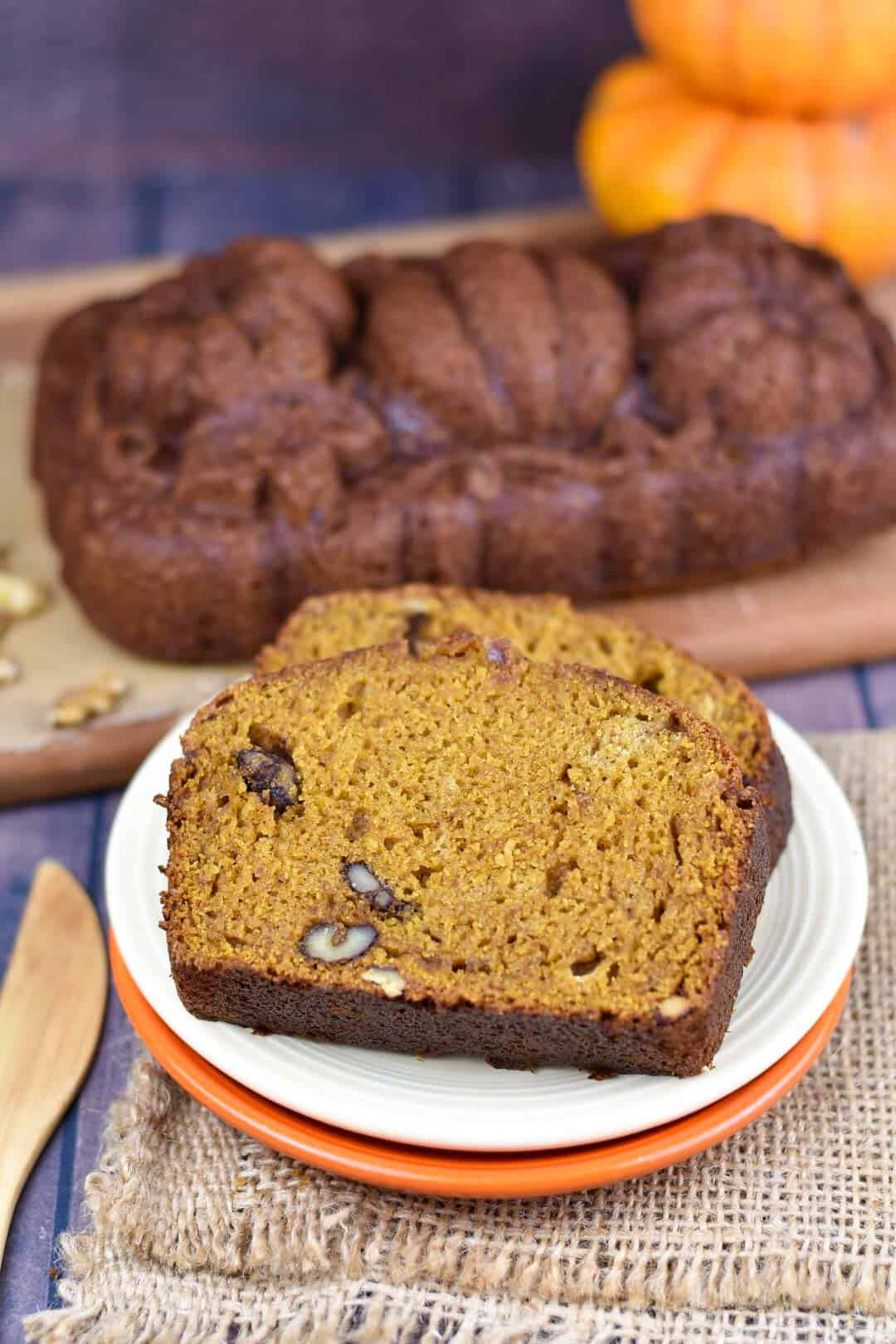 two slices of pumpkin walnut bread on platter with loaf in background