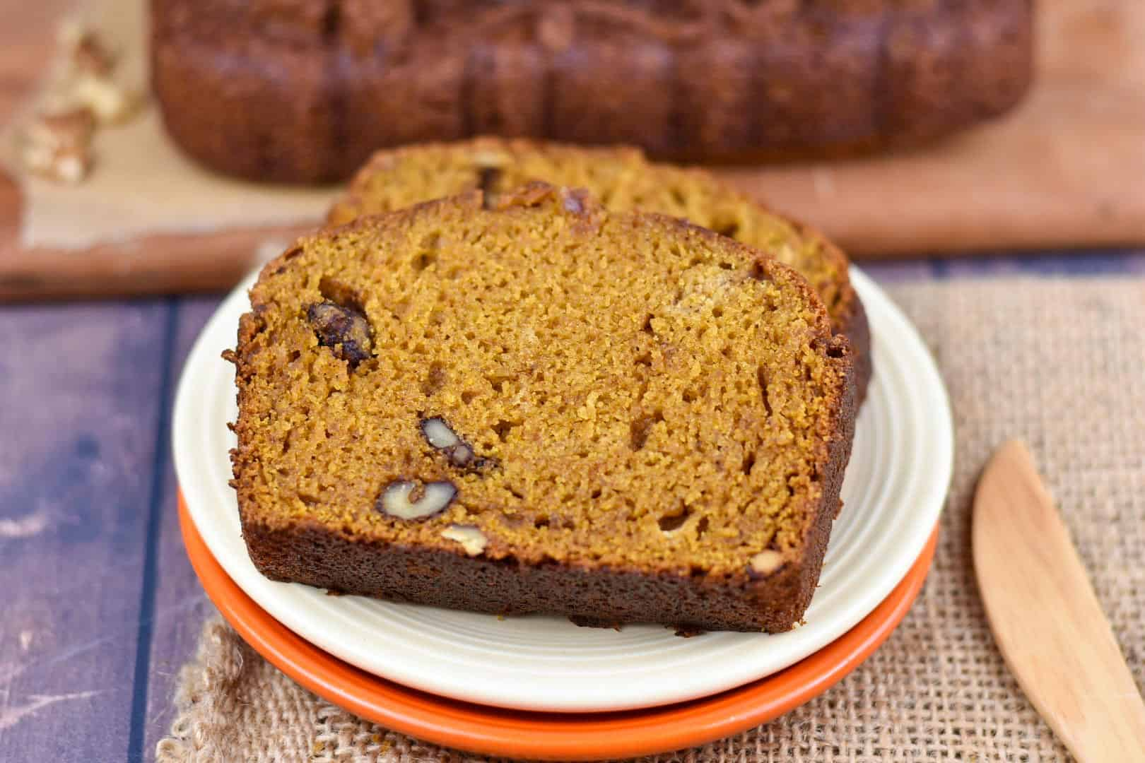 closeup images of two slices of pumpkin walnut bread on a plate